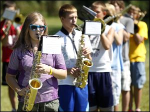 Freshman Lindsay Douglas, front, wears a pair of shades while reading the music to play her alto sax during practice outdoors on the school's lawn.