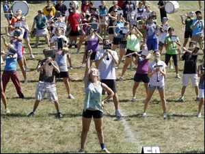 Sophomore Maddie Ruter, center, thrusts her baton high in the air as the song ends during the Sylvania Northview band's outdoor practice ahead of Friday night's home football game.