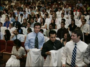 Medical students, from left, Trevor Carroll of Springfield, Ohio, Kristopher Carbone, of Maumee, and Gram Buchanan, of Springfield, Ohio, wait near the stage to have their white coats put on them during the White Coat Ceremony at UT's Nitschke Auditorium in Toledo.