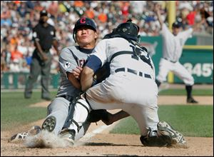 Cleveland's Kosuke Fukudome is tagged out by Detroit catcher Alex Avila on a throw from center fielder Austin Jackson to end the game.