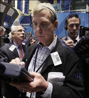 In this Aug. 19, 2011 photo, trader Richard Cohen, foreground center, on the floor of the New York Stock Exchange.