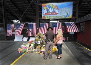 Fairgoers stop and pay their respects at the make-shift memorial for the six victims of a stage collapse just before Sugarland was to perform on the last day of the Indiana State Fair.
