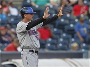 Buffalo manager Tim Teufel signals to a runner to stay where he is on the field.