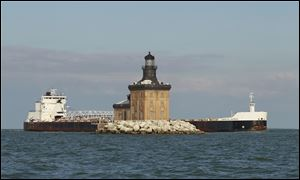 The freighter American Mariner sails behind the Toledo Harbor Lighthouse in the shipping lane. The lighthouse will welcome its first visitors Saturday.