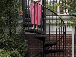 Jill Keller stands on her spiral staircase that connects the garden with the upper patio and sun room on August 3, 2011.