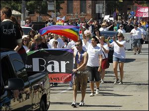 Marchers take part in the Toledo Gay Pride parade downtown.
