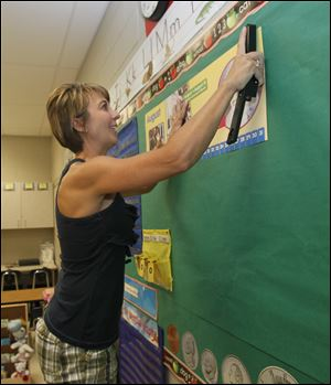 Kindergarten teacher Cathy Harris sets up her classroom at DeVeaux for incoming students. DeVeaux has been transformed from a middle school to a K-8 school.