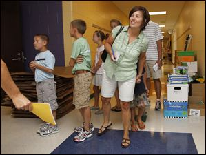 Tricia Cowell peaks into a classroom during a tour of the new Beverly K-8 School. All six of her children will attend the school.