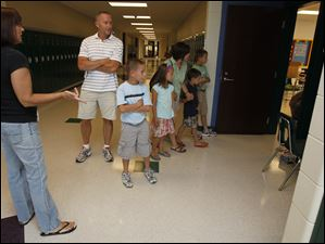 Sixth grade teacher Margaret Brandel, left, gives a tour to the Cowell family, from left, Steve, Sam (3rd grade), Jane (1st grade), Tricia, Jack (kindergarten), and Max (5th grade) during a tour of the new Beverly Elementary School.