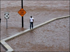 A man walks on top of a wall next  to a flooded highway in New Brunswick, N.J., Sunday as heavy rains left by Hurricane Irene are causing inland flooding of rivers and streams.  Flood waters rose all across New Jersey on Sunday, closing roads from side streets to major highways as Irene weakened and moved on.