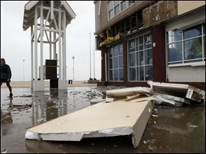 A man walks past a damaged store front on a boardwalk in Ocean City, Md., Sunday after Hurricane Irene churned along the Maryland coast overnight.