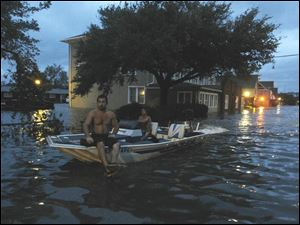 Two men use a boat to explore a street flooded by Hurricane Irene Saturday in Manteo, N.C.