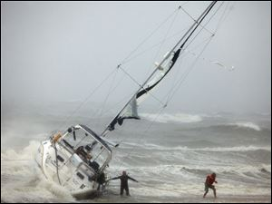 One of two people rescued from a sailboat, right, uses a line to make their way onto the beach on Willoughby Spit in Norfolk Saturday morning after they and another person were rescued from the boat that foundered in the waters of the Chesapeake Bay. A rescuer, left, waits for s second person to exit the boat.