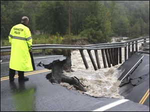 Bennington Police Chief Paul Doucette looks at a collapsed bridge on Route 9 in Woodford, Vt. on Sunday.