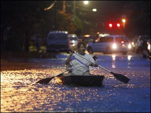Two men paddle a boat down a street flooded by rain from Hurricane Irene Saturday in Monteo, N.C.