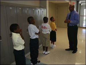 Principal Anthony Bronaugh, right, stops to compliment a group of students who are waiting patiently, quietly, and in line for their classmates.