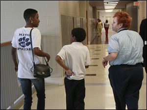 Trisicha Hicks, left, talks with Tracy Lustic, right, as Ms. Hicks' son, Jordan Crutchfield, a fourth-grader, tucks his shirt in on the way to his classroom. Ms. Lustic, a family support coordinator at Robinson, was one of the many school personnel who were placed around the building to help students get to where they needed to go. Crutchfield was a student at Martin Luther King, Jr. Academy last year, but