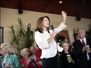 Republican presidential candidate Michele Bachmann talks to a group of supporters on the porch of Calistoga Bakery Cafe in Naples, Fla., on Monday, Aug. 29, 2011, during a campaign stop.
