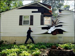Darrell Tarte, a property estimator with Erie Insurance, surveys damage from a tree at a home in Port Republic, Md. after Hurricane Irene Sunday, Aug. 28, 2011. Hurricane Irene left nearly a million people without power in the Mid-Atlantic region Sunday, filling low-lying roads with water and bringing trees down on power lines, streets and rail tracks.
