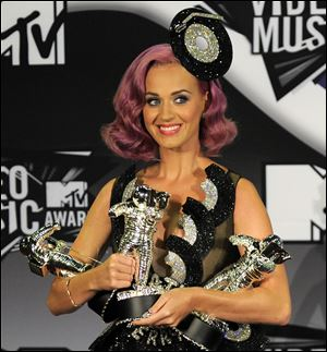 Katy Perry poses with her awards backstage at the MTV Video Music Awards on Sunday.
