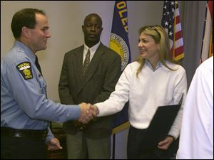 Navarre shakes the hand of dispatcher Julie Coupe as Detective Tim Campbell looks on Oct. 1, 2000, as they and several Toledo Police Department members were honored by the United States Postal Service for their efforts to identify and quickly make an arrest in the assault on a letter carrier.