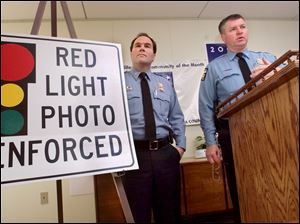 Toledo Police Chief Mike Navarre, left, and Lt. Lou Borucki talk about the red light camera program at city intersections during a December 21, 2000, press conference.