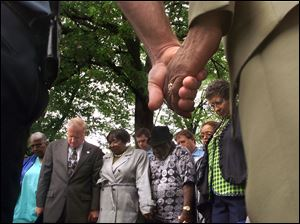 Toledo Police Chief Mike Navarre joins hands with Rev. Robert Culp during a prayer for murder victim Jerome Morgan at a press conference on gang violence May 15, 2001. Also attending were, background from left, Mayor Carty Finkbeiner, councilwoman Edna Brown, Blockwatch leader Frank Quinn, and councilwoman Wilma Brown.