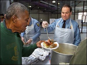 Roy Williams gets a ladle of gravy from Toledo Police Chief Mike Navarre at a holiday luncheon for folks with limited resources Nov. 16, 2000, at the Erie Street Market.