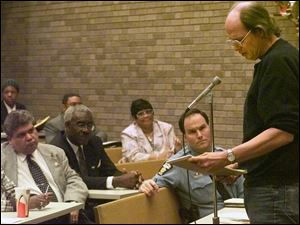 Navarre listens as Steve Miller, right, reads a statement on concern for others by the late Rev. Martin Luther King, Jr., at a public forum on community tensions March 9, 2000, at the University of Toledo's Law School. At left are Toledo City Council members Louis Escobar and Arthur Jones.