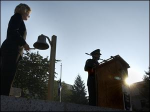 Police Chief Mike Navarre reads names of people killed in the 9/11 terrorist attacks during a memorial service on the Civic Center Mall in downtown Toledo on Sept. 11, 2003, as State Representative Teresa Fedor rings a bell for each name.