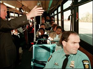 Mayor Carty Finkbeiner speaks to officials on a TARTA bus while Police Chief Mike Navarre looks out the window Oct. 19, 1999, during a tour of businesses with new locations from the Jeep plant location.