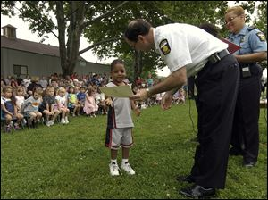 Camari Douglas, 4, gets a certificate from Toledo Police Chief Mike Navarre at a Safety City graduation ceremony June 18, 2004. At right is Officer Starr Chong.