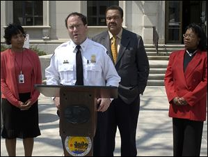 Navarre discusses the steps the city is taking to expand the national notification system for felony crimes at an April 2005 press conference. Behind him are, from left, councilwoman Karyn McConnell Hancock, Mayor Jack Ford, and clerk of courts Vallie Bowman English.