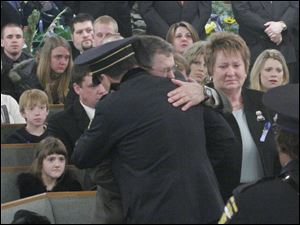 Michael Dressel, with wife Larraine Dressel, gets a hug from Toledo Police Chief Mike Navarre at the funeral for their son, Detective Keith T. Dressel, on Feb. 26, 2006, at Our Lady of Mount Carmel Church in Temperance, Mich..