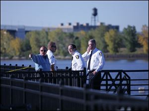 Chief Navarre, third from left, talks with officers at The Docks along the Maumee River where the body of  Dr. Shankar Palaniappan of Ann Arbor, Mich., had been found wedged partially under the dock Oct. 15, 2005.