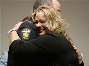 Danielle Dressel, widow of slain Detective Keith Dressel, hugs Chief Mike Navarre on May 18, 2007, as he presents her with the Distinguished Service Award, the Professional Service Award, the Medal of Valor, and the Blue Star Medal, on behalf of her late husband.