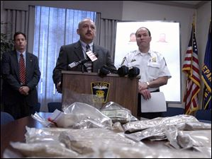 Chief Navarre looks on as Carl Spicocchi of the FBI speaks at a press conference May 20, 2005, about the seizure of 18.5 kilograms of heroin with a street value of $4 million to $6 million.