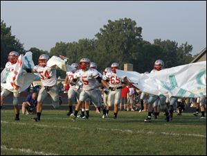 Central Catholic players charge onto the field to play Bedford High School at Bedford Community Stadium.