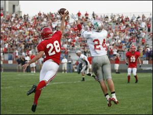 Bedford's Thomas Ferry (28) knocks away a pass intended for Central Catholic player Derich Weiland (24).