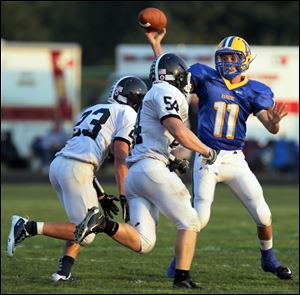 Lake defenders Tim Lohmann (23) and Zach Sharpe (54) puts pressure on Northwood quarterback Nick Russell.