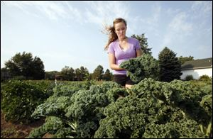 Alexandra Reau picks kale in her garden.