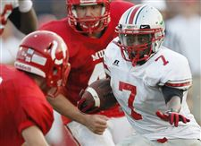 Central-Catholic-running-back-Cedric-Gray-dashes-by-Bedford-High-School-football-player-Thomas-Ferry