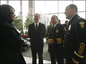 Shirley Green, left, appointee for Safety Director speaks with David Welch, from second left, incoming Director of Public Services, Fire Chief Mike Wolever, and Police Chief Michael Navarre on Dec. 22, 2009, at One Government Center.