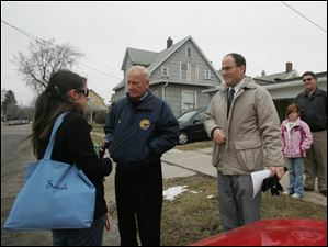 Mayor Carty Finkbeiner, center, and Toledo Police Chief Mike Navarre, right, speak with Sarah Huss, left,  about her vehicle being vandalized.