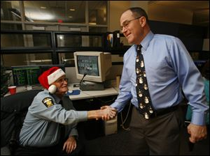 Toledo Officer James B. Ogle is greeted by Chief Mike Navarre before giving his 35th Santa Watch radio dispatch Dec. 24, 2009.