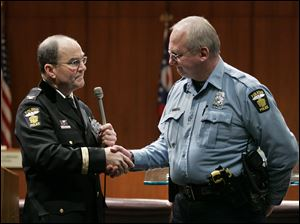 Chief Mike Navarre presents badge No.1 to Officer Robert Adams during a Toledo police department promotions ceremony Feb. 17, 2010, for Adams being the most senior officer in the department.