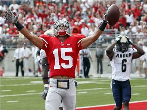Ohio State's Devin Smith (15) celebrates scoring a touchdown as Akron defender Manley Waller (6) reacts during the fourth quarter.