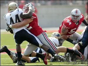 Ohio State's Andrew Sweat (42) buries Akron's Jawon Chisholm (44) in the back field.
