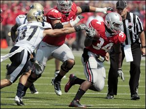 Ohio State's Carlos Hyde (34) runs the ball against Akron's Seth Cunningham (37) during the second quarter.