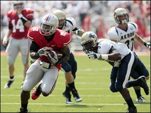 Ohio State's Rod Smith (2) runs with the ball against Akron's ShelDon Miller (32) during the first quarter.